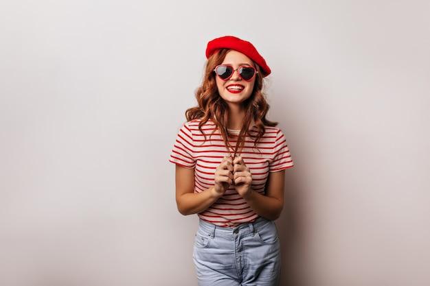 Adorável garota caucasiana com cabelo ruivo brincando. foto de senhora francesa satisfeita usa óculos de sol legais.