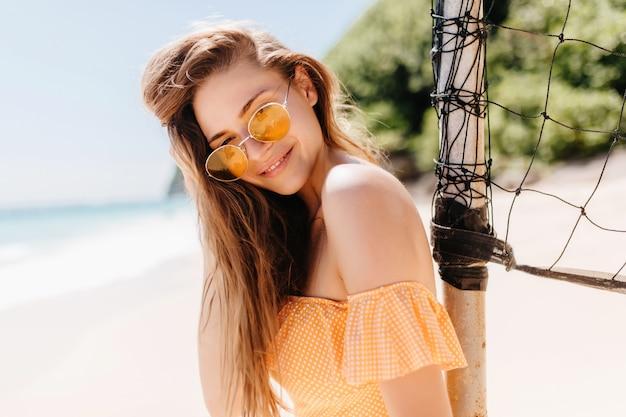 Adorável garota caucasiana olhando com interesse enquanto relaxa na ilha exótica. mulher bronzeada sonhadora em óculos de sol em pé perto do conjunto de voleibol.