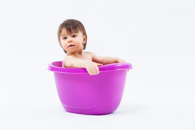 Adorável garota caucasiana tomando banho na banheira roxa em branco
