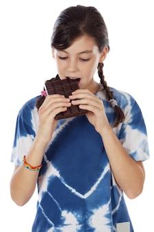 Adorável garota comendo chocolate um fundo branco