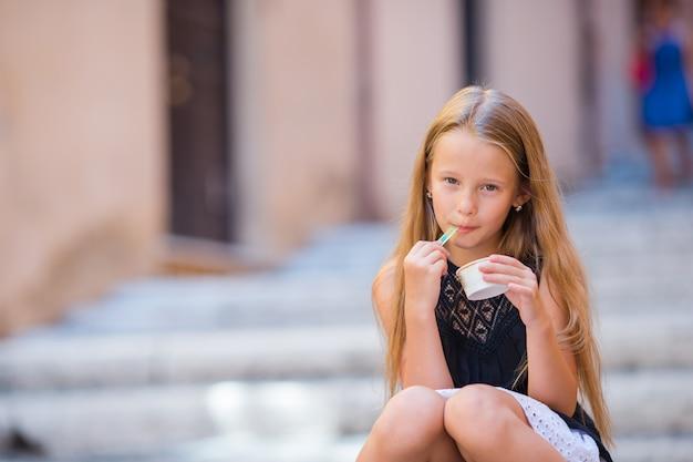 Adorável garota comendo sorvete ao ar livre no verão na cidade