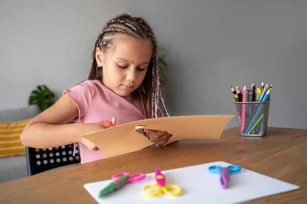 Adorável garota cortando papel com uma tesoura