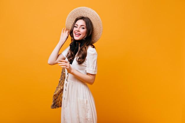 Adorável garota de cabelos escuros em um vestido de algodão branco sorri, segurando um chapéu de aba larga e uma bolsa de barbante.