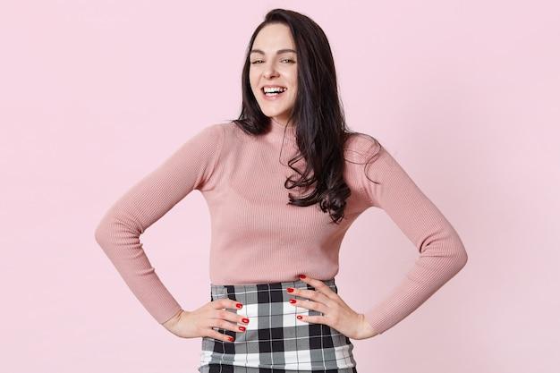 Adorável garota de cabelos escuros na camisa rosa e saia xadrez, posando com as mãos nos quadris, rindo enquanto olha para a câmera, ouve piada engraçada