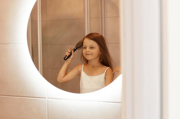 Adorável garota de cabelos escuros penteando o cabelo no banheiro em frente ao espelho, olhando seu reflexo, fazendo procedimentos de beleza matinais, expressando felicidade.