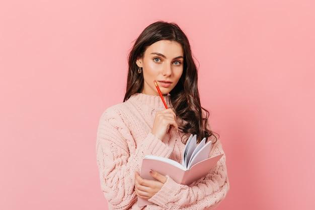 Adorável garota de olhos azuis posando pensativamente em fundo rosa. senhora de cabelo encaracolado, segurando o diário e o lápis vermelho.