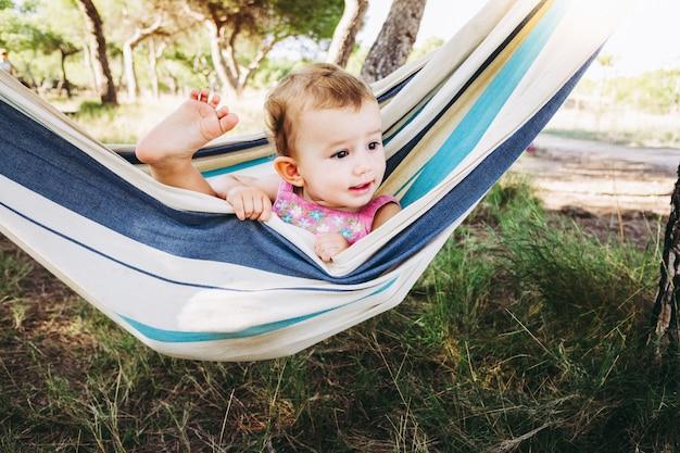 Adorável garota de um ano dentro de uma rede, sorrindo e se divertindo.