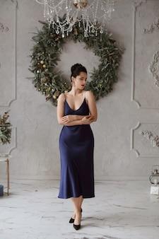 Adorável garota em um elegante vestido azul escuro na frente de decorações de natal adorável modelo feminino em ...