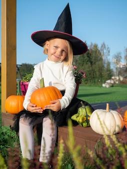 Adorável garota fantasiada de bruxa sentada com abóboras em um terraço de madeira