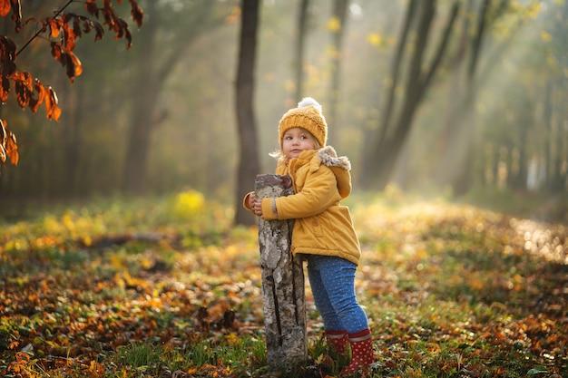 Adorável garota feliz brincando no parque outono