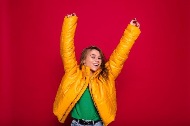 Adorável garota feliz com cabelo comprido, vestida com uma jaqueta de inverno amarela, posando com as mãos levantadas no vermelho