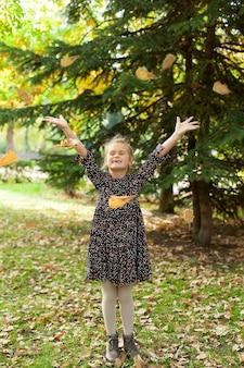 Adorável garota feliz jogando as folhas caídas, brincando no parque outono.