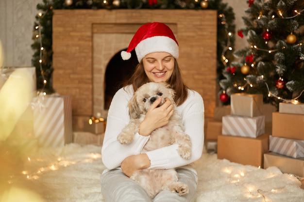 Adorável garota feliz no chapéu vermelho, abraçando-se com o lindo cão pequinês pela árvore de natal com luzes, lareira e caixas de presente na sala festiva, fêmea senta-se no chão e se divertindo com o cachorro.