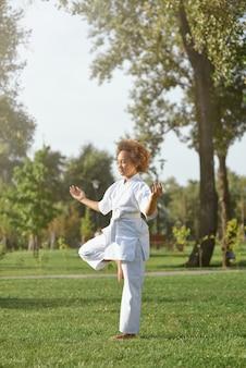 Adorável garota karateca fazendo exercícios na rua