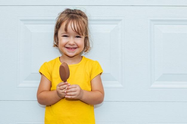 Adorável garota loira tomando sorvete, vestindo uma camisa amarela encostada em um fundo branco