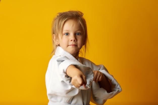 Adorável garota lutando no quimono branco