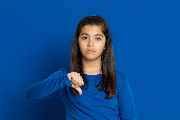 Adorável garota pré-adolescente com camisa azul, gesticulando sobre parede azul