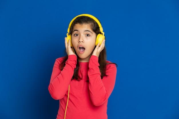 Adorável garota pré-adolescente com camisa vermelha, gesticulando sobre parede azul