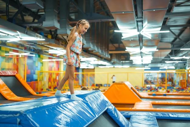 Adorável garota pulando na cama elástica de crianças, playground no centro de entretenimento.
