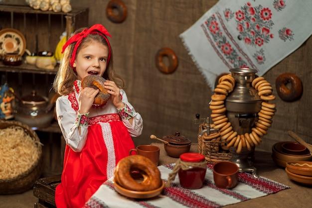 Adorável garota sentada à mesa cheia de comida e um grande samovar tra