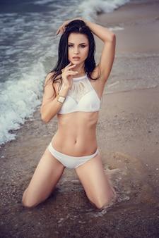 Adorável garota sexy de biquíni, aproveitando o verão. retrato ao ar livre. ondas do mar e espuma branca. pôr do sol após a chuva na ilha