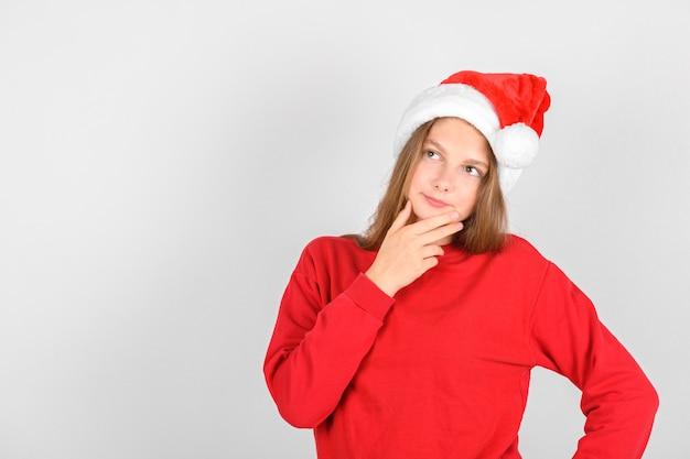 Adorável garota sorridente com chapéu de papai noel vermelho e pulôver vermelho