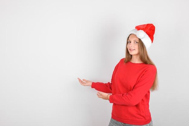 Adorável garota sorridente com chapéu de papai noel vermelho vestindo pulôver vermelho fazer um gesto: mostrando. fundo de venda de natal