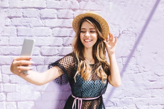 Adorável garota sorridente com um chapéu de palha da moda fazendo selfie enquanto espera um amigo lá fora