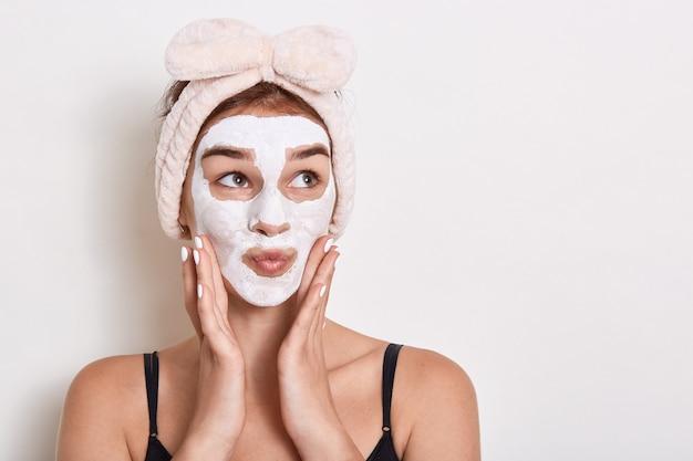 Adorável garota surpresa com bandana na cabeça, tendo expressão facial de espanto, posando isolado sobre um fundo branco, olhando para o lado, mantendo as mãos no rosto.