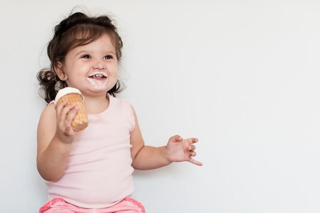 Adorável garota tomando sorvete e olhando para longe