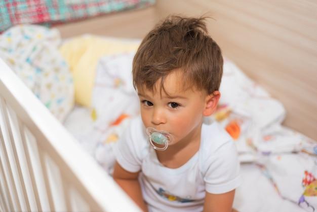 Adorável garotinho no berço com chupeta