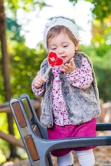 Adorável garoto com doces ao ar livre.