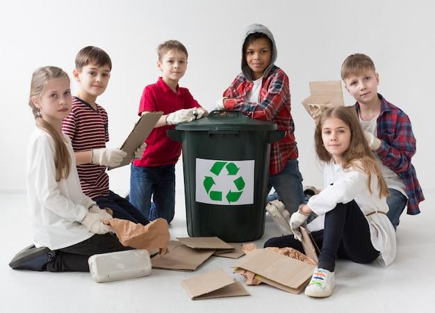 Adorável grupo de crianças reciclando juntos