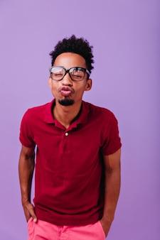 Adorável homem africano de pé na parede violeta pastel. cara de cabelos escuros posando com expressão de rosto de beijo.