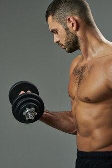 Adorável homem atleta tonificando os músculos em uma sala dentro de casa
