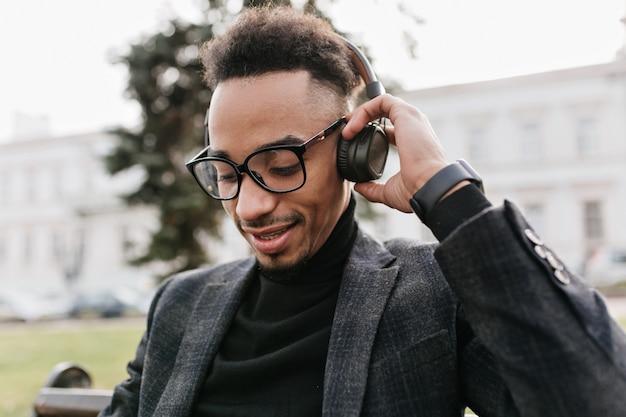 Adorável homem negro com penteado afro, tocando seus fones de ouvido. retrato ao ar livre do modelo masculino africano com roupas cinza, descansando no banco pela manhã.