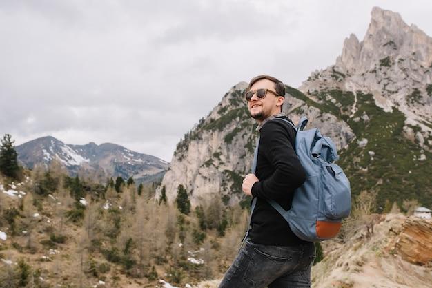 Adorável homem usando óculos escuros escalando montanhas e olhando para longe, segurando uma mochila azul