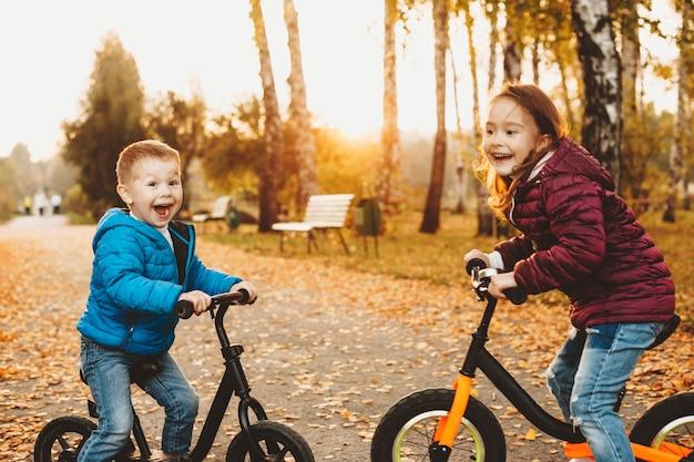 Adorável irmão e irmã se divertindo, rindo, sentados cara a cara em suas bicicletas no parque contra o pôr do sol.