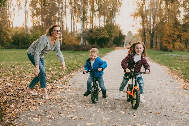 Adorável irmãozinho competindo com sua irmã andando de bicicleta ao ar livre no parque enquanto sua mãe está dando a partida.