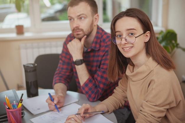 Adorável jovem adolescente trabalhando em um projeto com seu professor