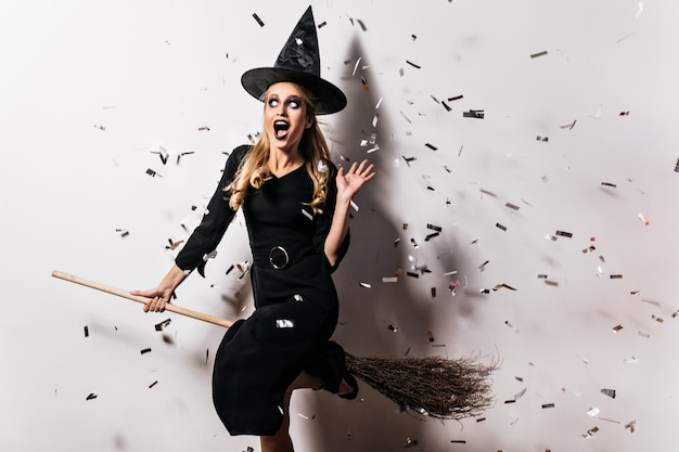 Adorável jovem bruxa sentada na vassoura. garota incrível com chapéu de halloween, posando na parede branca.