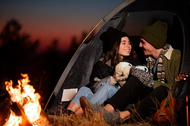 Adorável jovem casal ao lado de uma fogueira