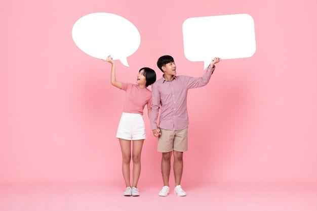 Adorável jovem casal asiático com bolhas do discurso