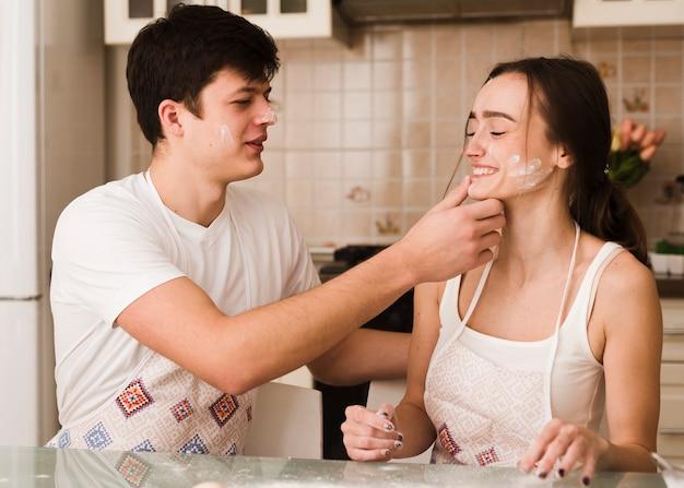 Adorável jovem casal brincando na cozinha