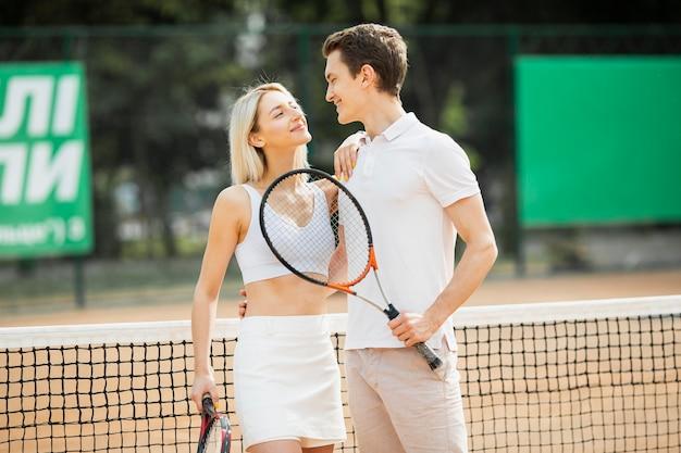 Adorável jovem casal na quadra de tênis