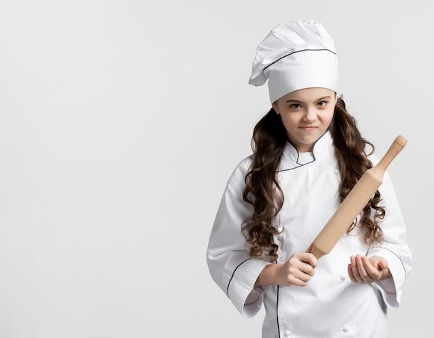 Adorável jovem chef segurando o rolo
