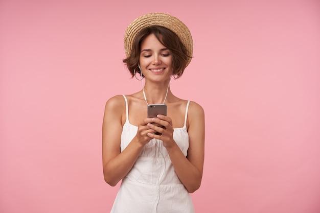 Adorável jovem com cabelo castanho curto, segurando o celular nas mãos e olhando animadamente na tela, assistindo vídeos agradáveis com fones de ouvido, isolado