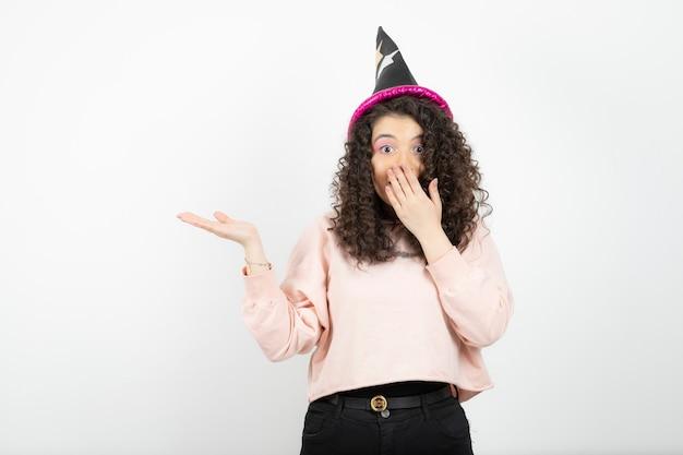 Adorável jovem com cabelo encaracolado, usando um chapéu especial para a festa.