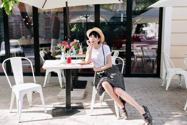 Adorável jovem com chapéu de verão descansando em um café ao ar livre com a mão apoiada no rosto e um amigo esperando