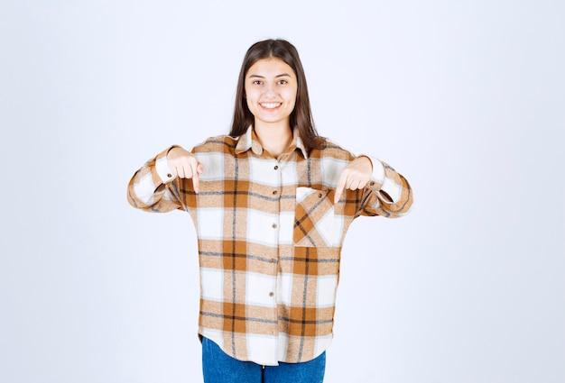 Adorável jovem com roupa casual, apontando para a desvantagem na parede branca.